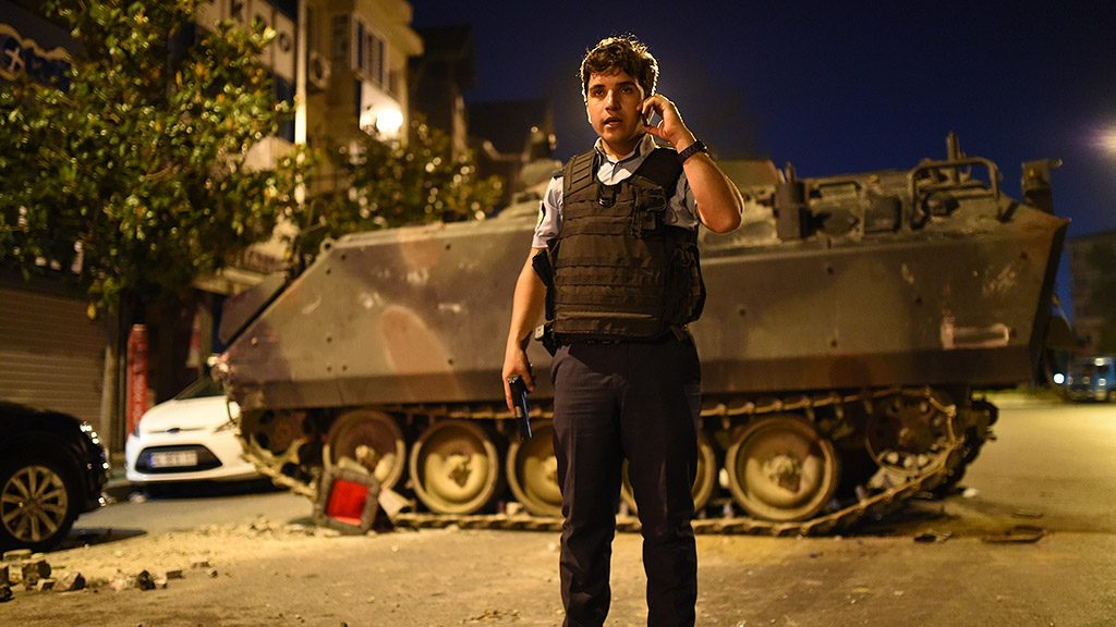 A Turkish police officer talks on a phone during clashes in Istanbul on July 16, 2016. At least 60 people have been killed and 336 detained in a night of violence across Turkey sparked when elements in the military staged an attempted coup, a senior Turkish official said. The majority of those killed were civilians and most of those detained are soldiers, said the official, without giving further details. / AFP PHOTO / Bulent KILIC