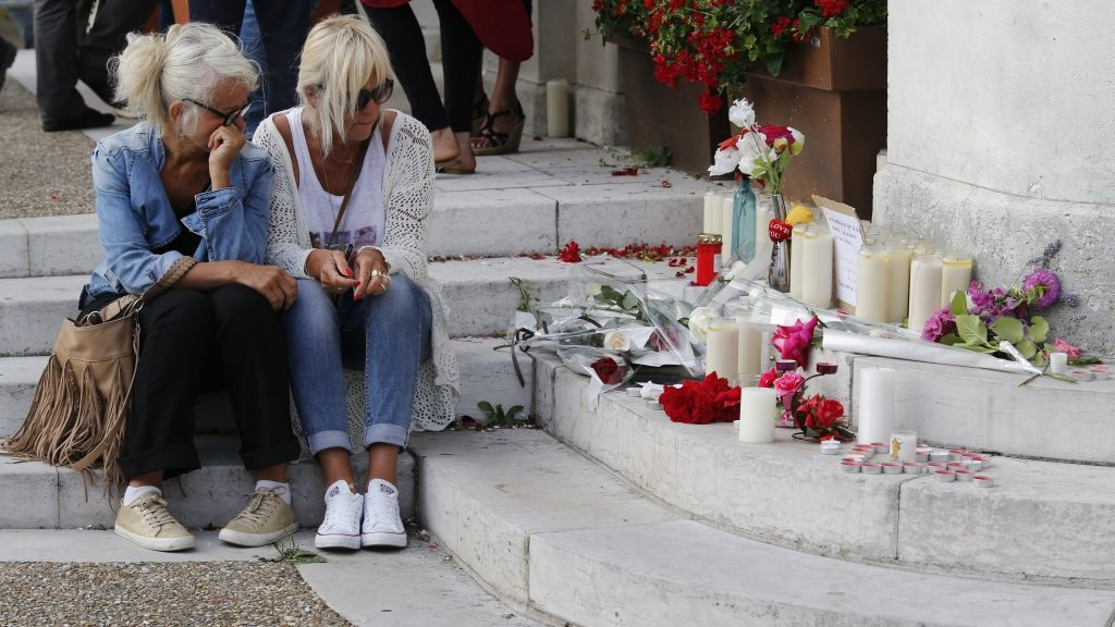 """Two women sit near candles and flowers displayed in front of the city hall of the Normandy city of Saint-Etienne du Rouvray on July 26, 2016 after a priest was killed in the latest of a string of attacks against Western targets claimed by or blamed on the Islamic State jihadist group. French President said that two men who attacked a church and slit the throat of a priest had """"claimed to be from Daesh"""", using the Arabic name for the Islamic State group. Police said they killed two hostage-takers in the attack in the Normandy town of Saint-Etienne-du-Rouvray, 125 kilometres (77 miles) north of Paris. / AFP PHOTO / MATTHIEU ALEXANDRE"""