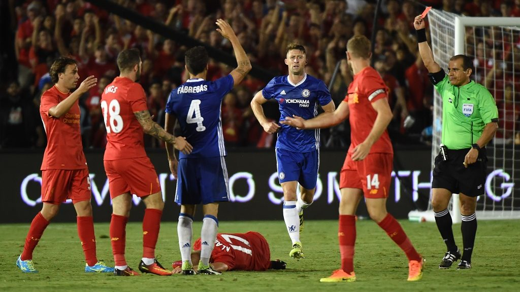 Chelsea midfielder Cesc Fabregas (3rd L) receives a red card after fouling Liverpool player Ragnar Klavan (on ground) during their International Champions Cup (ICC) game at the Rose Bowl Stadium in Pasadena, California on July 27, 2016. Chelsea won 1-0. / AFP PHOTO / Mark Ralston