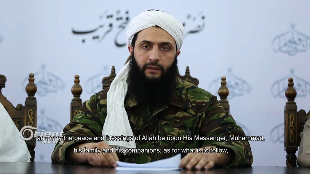 """An image grab taken from a video broadcast on July 28, 2016 by Dubai-based Orient News satellite television shows the head of Al-Nusra Front in Syria, Abu Mohamad al-Jolani, giving a speech from an undisclosed location, in the first ever video showing his face to be released. Jolani said his jihadist group was breaking ties with Al-Qaeda and changing its name to Jabhat Fateh al-Sham (Conquest of Syria in Arabic). Al-Nusra, an offshoot of the Islamic State in Iraq, Al-Qaeda's former Iraqi affiliate, first emerged in January 2012 -- 10 months after the start of anti-government protests that were brutally repressed by the Assad regime, leading to a multi-sided conflict which continues today. The Arabic writing reads: """"Soon, a televised speech by Sheikh Abu Mohammad al-Jolani."""" / AFP PHOTO / Orient News / HO / RESTRICTED TO EDITORIAL USE - MANDATORY CREDIT """"AFP PHOTO / HO / ORIENT NEWS"""" - NO MARKETING NO ADVERTISING CAMPAIGNS - DISTRIBUTED AS A SERVICE TO CLIENTS FROM ALTERNATIVE SOURCES, AFP IS NOT RESPONSIBLE FOR ANY DIGITAL ALTERATIONS TO THE PICTURE'"""