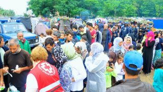 HORGOS, SERBIA - JULY 17: Members of charities distribute food aid in Horgos, Serbia on July 17, 2016. A total number of 545 refugees, mostly Afqhans have been waiting to cross to Hungary after Hungarian officials tightened the border security since 5th of July. Talha Ozturk / Anadolu Agency
