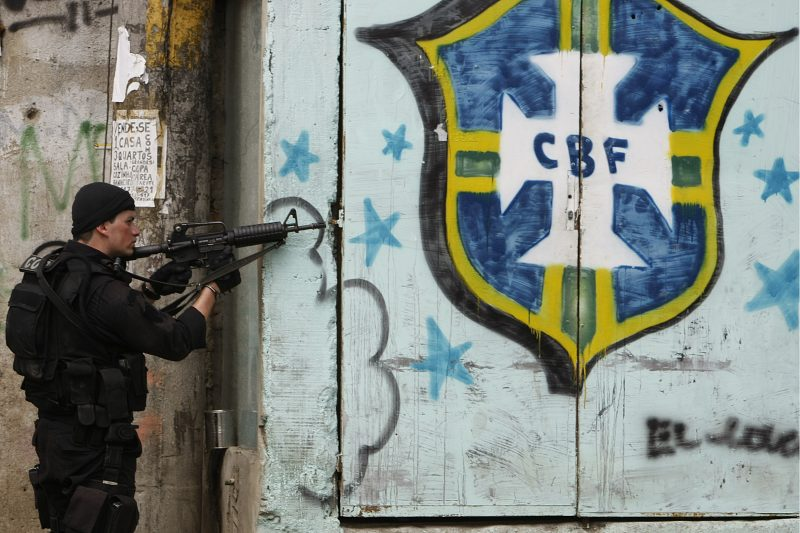 RIO DE JANEIRO, BRAZIL - NOVEMBER 25:(FILE)  Police officers of the Special Operations Battalion (BOPE) are seen patroling next to a CBF logo at Vila Cruzeiro during the fifth day of a wave of violence on November 25, 2010 in Rio de Janeiro, Brazil. Since November 21th, 23 people died, more than 30 vehicles were torched and 153 people were arrested or detained. The assaults are being considered by authorities an answer to the Rio's Peacemaker Police Units (UPP), installed in several slums of the city. These are now under control of the criminal factions Comando Vermelho and ADA. Rio de Janeiro will host the next FIFA Confederations Cup in 2013, the FIFA World Cup in 2014 and the Olympic and Paralympic Summer Games in 2016. (Photo by Buda Mendes/LatinContent/Getty Images)