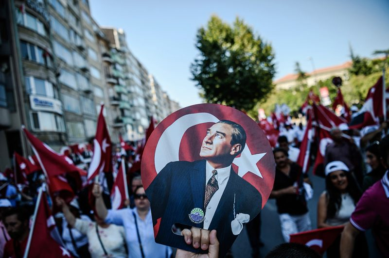 """A Demonstrator holds a poster of Mustafa Kemal Ataturk, founder of modern Turkey, as others wave Turksih national flags in Istanbul on July 24, 2016 during the first cross-party rally to condemn the coup attempt against President Recep Tayyip Erdogan. Many thousands of flag-waving Turks massed on July 24, 2016, for the first cross-party rally to condemn the coup attempt against President Recep Tayyip Erdogan, amid an ongoing purge of suspected state enemies. Several banners also protested the post-coup state of emergency, with one proclaiming """"No to the coup, no to dictatorship"""" and another saying """"Turkey is secular and will remain so"""". The mass event was called by the biggest opposition group, the secular and centre-left Republican People's Party (CHP), many of whose members carried pictures of modern Turkey's founding father Mustafa Kemal Ataturk. / AFP PHOTO / OZAN KOSE"""