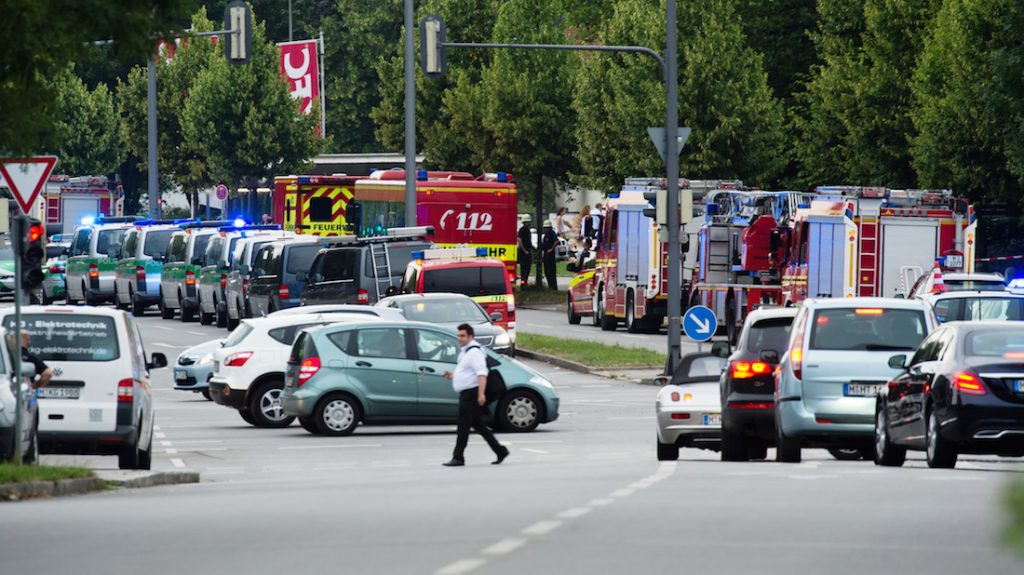 Police and firefighters are seen near a shopping mall amid a shooting on July 22, 2016 in Munich. Several people were killed on Friday in a shooting rampage by a lone gunman in a Munich shopping centre, media reports said / AFP PHOTO / dpa / Matthias Balk / Germany OUT