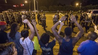 """BATON ROUGE, LA -JULY 10: Protesters shout """"Hands up, don't shoot"""" as law enforcement gather before charging the protesters to make arrests on July 10, 2016 in Baton Rouge, Louisiana. Alton Sterling was shot by a police officer in front of the Triple S Food Mart in Baton Rouge on July 5th, leading the Department of Justice to open a civil rights investigation.   Mark Wallheiser/Getty Images/AFP / AFP PHOTO / GETTY IMAGES NORTH AMERICA / MARK WALLHEISER"""