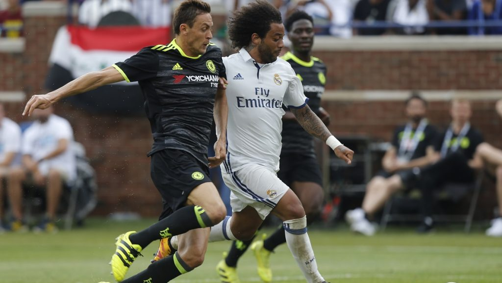 Real Madrid defender Marcelo Vieira da Silva (R) dribbles the ball past Chelsea defender Gary Cahill (L) during an International Champions Cup soccer match in Ann Arbor, Michigan on July 30, 2016. / AFP PHOTO / Jay LaPrete