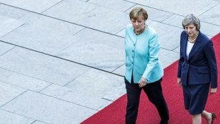 BERLIN, GERMANY - JULY 20: German Chancellor Angela Merkel and British Prime Minister Theresa May walk on a red carpet while reviewing a guard of honor upon May's arrival at the Chancellery on July 20, 2016 in Berlin, Germany. May, who replaced David Cameron as prime minister last week in the wake of the Brexit vote that will take the United Kingdom out of the European Union, is visiting Germany and France in her first foreign trip since assuming office. (Photo by Carsten Koall/Getty Images)