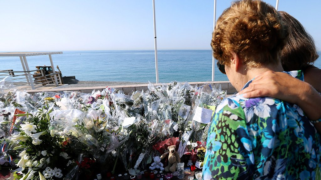 People stand by the new makeshift memorial in tribute to the victims of the deadly Bastille Day attack at the Promenade des Anglais,  on July 19, 2016 in Nice, after it was moved from the pavement of the road to the seafront so that the street can be re-opened.The Islamic State group claimed responsibility for the truck attack that killed 84 people in Nice on France's national holiday, a news service affiliated with the jihadists said on July 16. Tunisian Mohamed Lahouaiej-Bouhlel, 31, smashed a 19-tonne truck into a packed crowd of people in the Riviera city celebrating Bastille Day -- France's national day. / AFP PHOTO / Valery HACHE