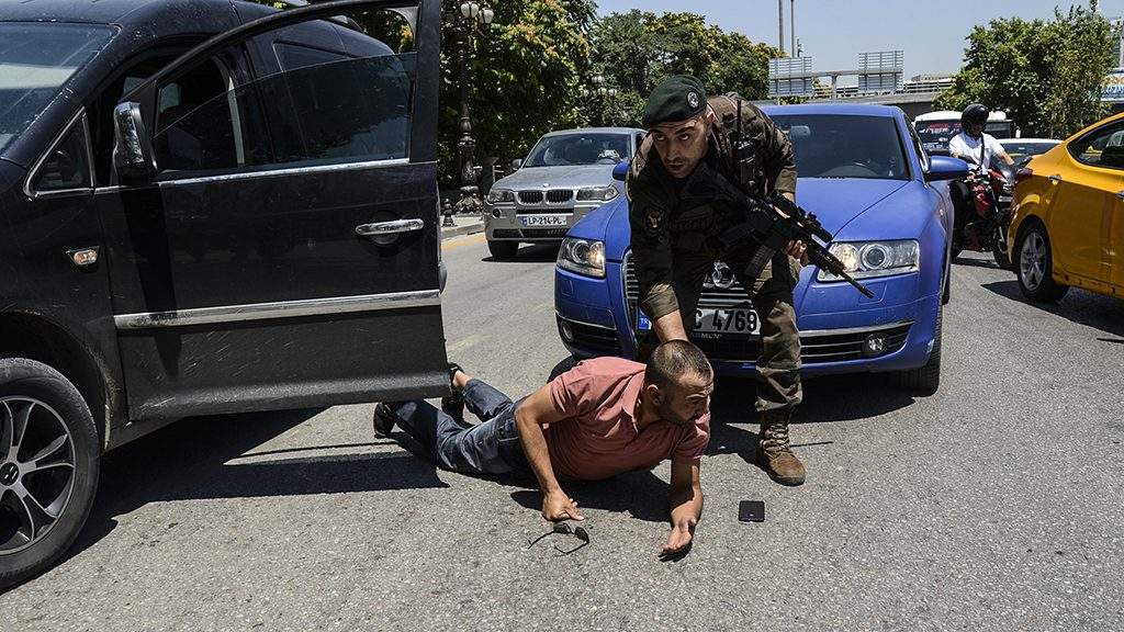A Turkish police restrains a man on the ground during an operation in front of the courthouse on July 18, 2016, in Ankara.Turkey has detained more than 7,500 suspects involved in the coup plot seeking to oust the government, the prime minister said on July 18, 2016. Giving a new toll, he said 208 people were killed by the coup bid, including 145 civilians, 60 police and three soldiers. 1,491 were wounded, he added, In addition, the authorities have said more than 100 coup plotters were killed. / AFP PHOTO / ILYAS AKENGIN