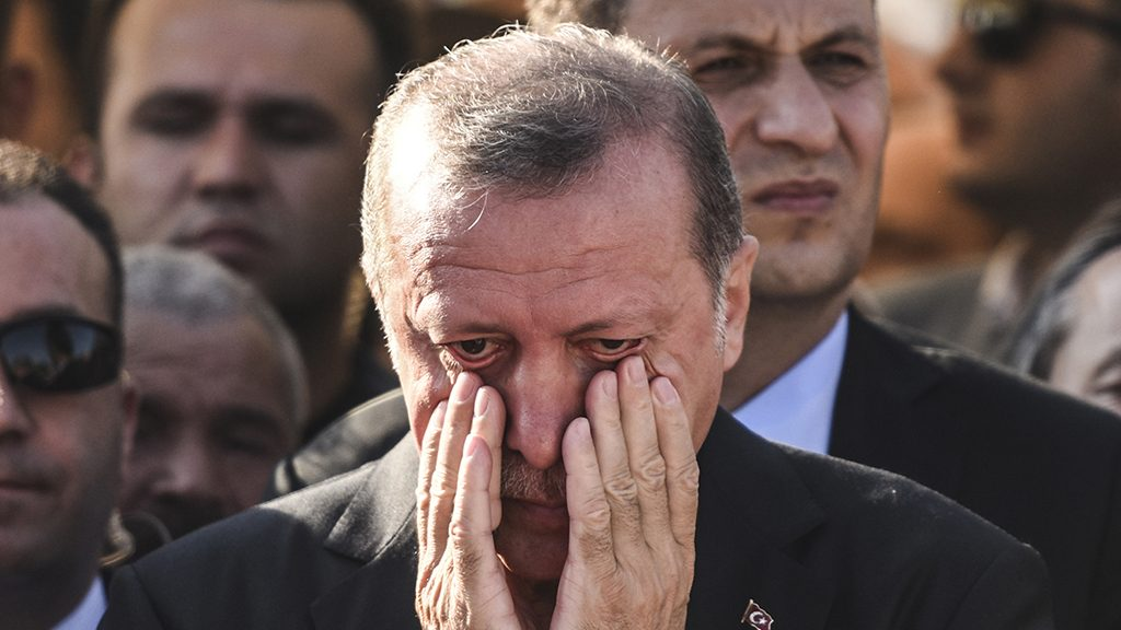 """Turkey's President Recep Tayyip Erdogan reacts after attending the funeral of a victim of the coup attempt in Istanbul on July 17, 2016. Turkish President Recep Tayyip Erdogan vowed today to purge the """"virus"""" within state bodies, during a speech at the funeral of victims killed during the coup bid he blames on his enemy Fethullah Gulen. / AFP PHOTO / BULENT KILIC"""