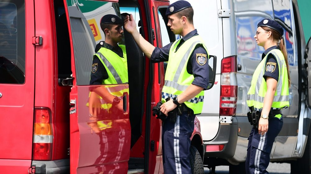 Austrian police officers search a van at the Austrian-Hungarian border of Nickeldsdorf on July 12, 2016.   It's holiday season at Nickelsdorf on Austria's border with Hungary as families hit the highway but although the streams of refugees seen here a year ago have gone, things are far from normal.  / AFP PHOTO / ATTILA KISBENEDEK