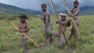 Dani tribesmen pose for photographs prior to performing a mock tribal war battle during the 27th annual Baliem Valley Festival in Walesi district in Wamena, Papua Province on August 9, 2016. Performances at the 27th Baliem Valley Festival, taking place from August 8 to 10, feature mock battles of highland tribes of Dani, Yali and Lani to symbolise the high spirit and power that have been practised for generations. / AFP PHOTO / ADEK BERRY
