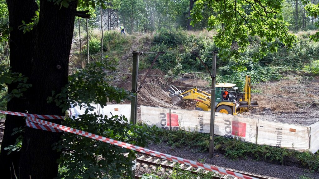 """Workers dig the ground as excavations are under way aiming to verify the existence of the so-called 'Nazi Gold train' in Walbrzych, Poland, on August 16, 2016. Piotr Koper and Andreas Richter, who reported finding the so-called 'Nazi Gold train"""" in August 2015, relaunched their search for a lost Nazi gold train allegedly loaded with loot and buried in southwestern Poland, despite there being no scientific evidence it exists. / AFP PHOTO / NATALIA DOBRYSZYCKA"""