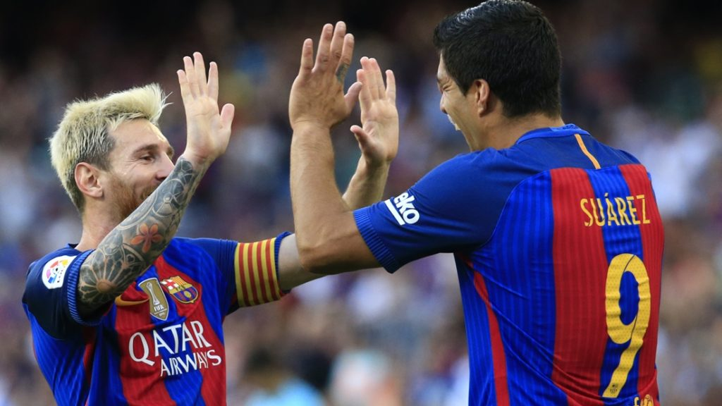 Barcelona's Uruguayan forward Luis Suarez (R) celebrates after scoring with Barcelona's Argentinian forward Lionel Messi during the Spanish league football match FC Barcelona vs Real Betis Balompie at the Camp Nou stadium in Barcelona on August 20, 2016. / AFP PHOTO / PAU BARRENA