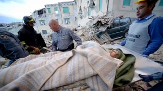 Rescuers carry a man from the rubble after a strong heartquake hit Amatrice on August 24, 2016.  Central Italy was struck by a powerful, 6.2-magnitude earthquake in the early hours, which has killed at least three people and devastated dozens of mountain villages. Numerous buildings had collapsed in communities close to the epicenter of the quake near the town of Norcia in the region of Umbria, witnesses told Italian media, with an increase in the death toll highly likely. / AFP PHOTO / FILIPPO MONTEFORTE