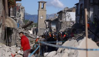 Rescuers and firemen inspect the rubble of buildings  in Amatrice on August 24, 2016 after a powerful earthquake rocked central Italy. The earthquake left 38 people dead and the total is likely to rise, the country's civil protection unit said in the first official death toll. Scores of buildings were reduced to dusty piles of masonry in communities close to the epicentre of the pre-dawn quake in a remote area straddling the regions of Umbria, Marche and Lazio. / AFP PHOTO / FILIPPO MONTEFORTE