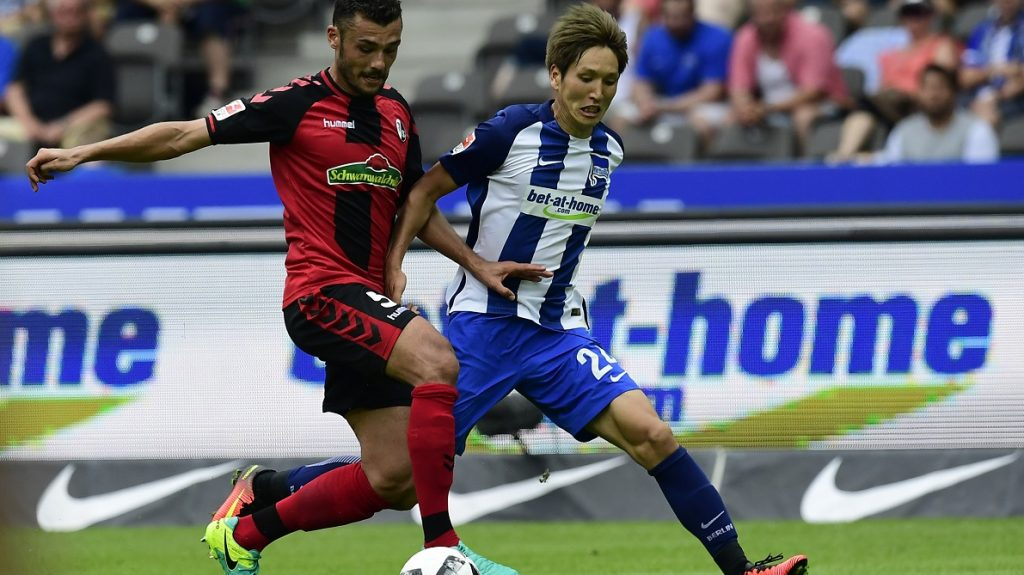 Freiburg's defender Manuel Gulde (L) and Berlin's Japanese midfielder Genki Haraguchi vie for the ballduring the German first division Bundesliga football match of Hertha BSC Berlin vs SC Freiburg in Berlin, Germany, on August 28, 2016.  / AFP PHOTO / TOBIAS SCHWARZ / RESTRICTIONS: DURING MATCH TIME: DFL RULES TO LIMIT THE ONLINE USAGE TO 15 PICTURES PER MATCH AND FORBID IMAGE SEQUENCES TO SIMULATE VIDEO. == RESTRICTED TO EDITORIAL USE == FOR FURTHER QUERIES PLEASE CONTACT DFL DIRECTLY AT + 49 69 650050