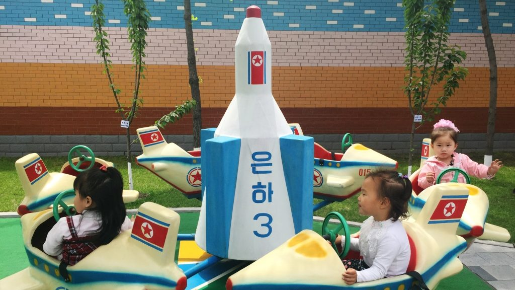 """2852284 05/09/2016 Children ride on a merry-go-round in the shape of """"Unha-3"""" (Milky way-3) in one of the kindergardens of Pyohgyang. ????? ??????/Sputnik"""