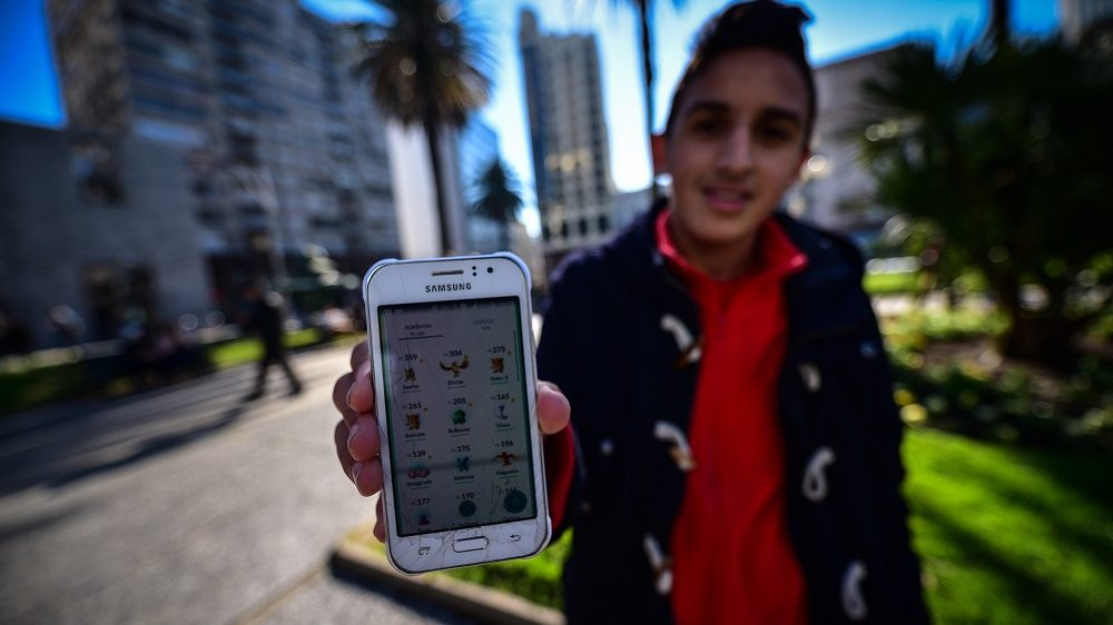 """MONTEVIDEO, URUGUAY - AUGUST 6: A boy shows the number of Pokémon that has hunted in the central square in Montevideo on August 6 2016. After a long wait, the popular game Pokémon Go was launched in Uruguay, and as might be expected, thousands of young people took the weekend to """"hunt"""" in the streets.  Carlos Lebrato / Anadolu Agency"""