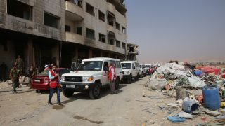 Red crescent ambulances and Syrian army soldiers gather in the government-controlled part of the besieged town of Daraya on August 26, 2016, as thousands of rebel fighters and civilians prepared to evacuate under an accord struck a day earlier.   An estimated 8,000 people remain in the town, despite a government siege lasting four years and regular regime bombardment.      / AFP PHOTO / Youssef KARWASHAN