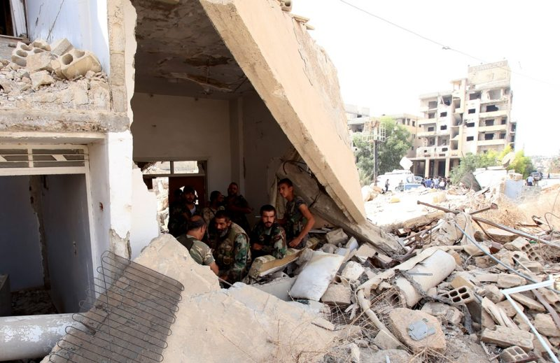 Syrian army soldiers gather at the entrance of a damaged building in the government-controlled part of the besieged town of Daraya on August 26, 2016, as thousands of rebel fighters and civilians prepared to evacuate under an accord struck a day earlier.  An estimated 8,000 people remain in the town, despite a government siege lasting four years and regular regime bombardment.    / AFP PHOTO / Youssef KARWASHAN