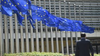 """EU flags fly at half-mast in front of the European Commission building in Brussels on July 15, 2016, following the attack in Nice where a truck crashed into the crowd during the Bastille Day celebrations.A Tunisian-born man zigzagged a truck through a crowd celebrating Bastille Day in the French city of Nice, killing at least 84 and injuring dozens of children in what President Francois Hollande on July 15 called a """"terrorist"""" attack. / AFP PHOTO / JOHN THYS"""