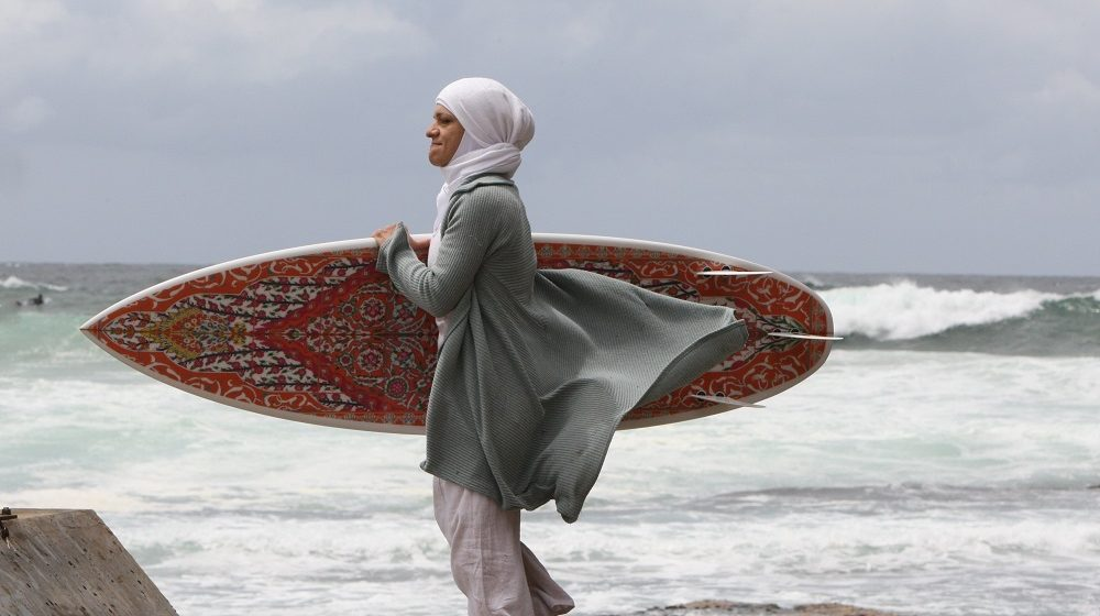 (AUSTRALIA OUT, NEW ZEALAND OUT)  NSW Uni College of Fine Arts lecturer and artist Phillip George has created Islamic decorated surfboards as part of an exhibition. Photos shows, Inventor of the Burqini Swim Suit Aheda  Zanett pictured with one of the surf boards at Bondi Beach.  Tuesday 25 November 2008.  (Photo by Peter Rae/Sydney Morning Herald/Fairfax Media via Getty Images)