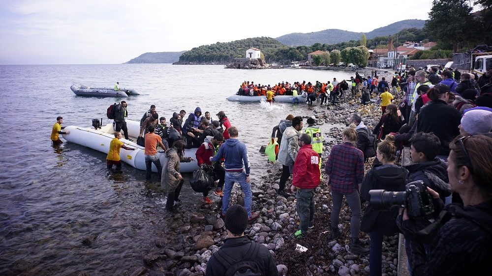 SIKAMINIAS, GREECE  - NOVEMBER 16:  Aid workers wade in the sea to help a migrant boat as it approaches shore after making the crossing from Turkey to the Greek island of Lesbos on November 16, 2015 in Sikaminias, Greece. Rafts and boats continue to make the journey from Turkey to Lesbos each day as thousands flee conflict in Iraq, Syria, Afghanistan and other countries. Over 500,000 migrants have entered Europe so far this year and approximately four-fifths of those have paid to be smuggled by sea to Greece from Turkey, the main transit route into the EU. Most of those entering Greece on a boat from Turkey are from the war zones of Syria, Iraq and Afghanistan. (Photo by Milos Bicanski/Getty Images)