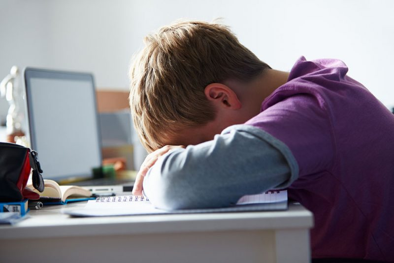 Tired Boy Studying In Bedroom With Head On Table Upset