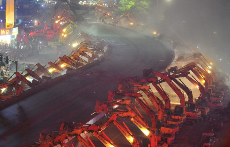 Night view of excavators demolishing the Yonghe Gate overpass in Nanchang city, east China's Jiangxi province, 26 August 2016.  Close to a hundred excavators tore down a highway overpass in eastern China overnight to pave way for the construction of a subway line, state media reported. At about 10:30pm on Friday (26 August 2016), 86 excavators lined up on both sides of the 500 metre elevated road in Nanchang, capital of Jiangxi province, and began pounding away with their wrecking hammers. The Yonghe Gate overpass was built above a main road connecting the city's southern and northern suburbs, and by the early Sunday morning, the 24-year-old structure had been reduced to piles of rubble. The bridge, named after the city's ancient former Yonghe Gate, was built in the 1990s at the height of a traffic infrastructure construction boom in the city. The overpass has helped ease traffic congestion on nearby roads nearby since its inception, but its closed design also prevents it from diverting vehicles to other routes once it becomes congested itself, according to the report carried on Thepaper.cn, a state-run news website based in Shanghai.