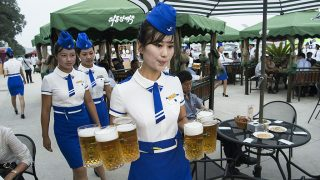 This photo taken on August 12, 2016 shows a waitress carrying jugs of beer to guests before the opening of the Pyongyang Taedonggang Beer Festival on the banks of the Taedong river in Pyongyang. / AFP PHOTO / Kim Won-Jin