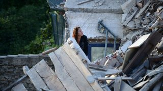 A woman looks at damaged buildings after a strong earthquake hit central Italy, in Amatrice on August 24, 2016.A powerful 6.2-magnitude earthquake devastated mountain villages in central Italy on Wednesday, leaving at least 18 people dead and dozens more injured or unaccounted for. Scores of buildings were reduced to dusty piles of masonry in communities close to the epicentre of the pre-dawn quake in a remote area straddling the regions of Umbria, Marche and Lazio. / AFP PHOTO / FILIPPO MONTEFORTE