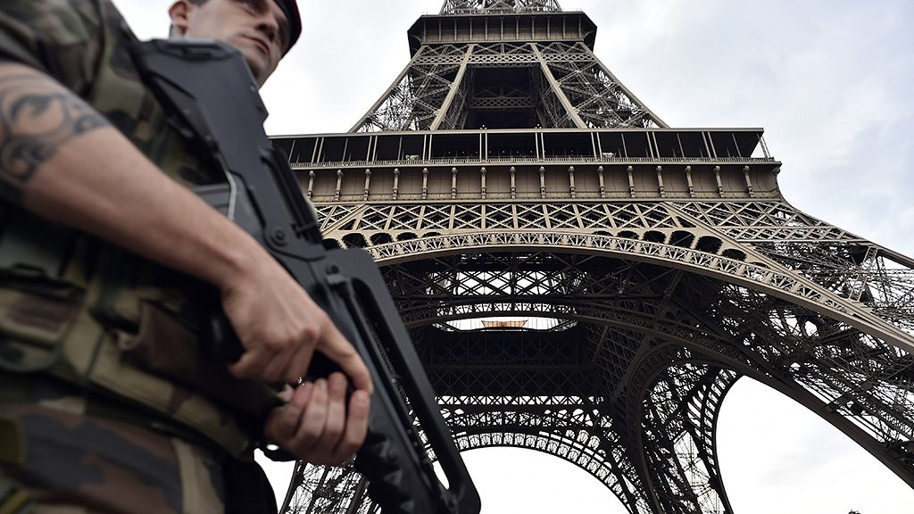 An armed French soldier of the 35th RAP (35e regiment d'artillerie parachutiste), part of Operation Sentinelle, patrols under at the Eiffel tower in Paris on July 20, 2016. / AFP PHOTO / ALAIN JOCARD