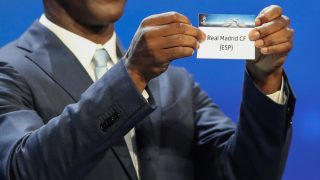 Dutch former football player Clarence Seedorf shows a piece of paper bearing the name of Real Madrid CF during the UEFA Champions League Group stage draw ceremony, on August 25, 2016 in Monaco. / AFP PHOTO / Valery HACHE