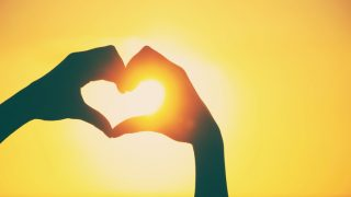 Love shape hands silhouette during sunset  with vintage and vignette effect