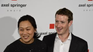 Facebook founder and CEO Mark Zuckerberg (R) arrives to receive the Axel Springer Award with his wife Priscilla Chan in Berlin on February 25, 2016.  Facebook announced it was donating computer servers to a number of research institutions across Europe, starting with Germany, to accelerate research efforts in artificial intelligence (AI) and machine learning.   / AFP PHOTO / John MACDOUGALL