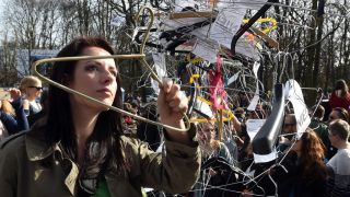 """A woman hangs up hangers, symbolizing illegal abortion, as demonstrators protest against a possible tightening of Poland's abortion law, already one of the most restrictive in Europe, in Warsaw on April 3, 2016. Rallies in Warsaw and other cities are being held under the slogan """"No to the Torture of Women"""" and come as the influential Roman Catholic church launches a campaign for a total ban on abortion, something supported by Prime Minister Beata Szydlo and ruling party leader Jaroslaw Kaczynski. / AFP PHOTO / JANEK SKARZYNSKI"""