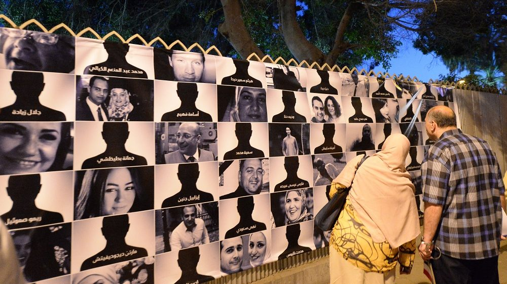 Egyptians look at posters of the 66 victims of the EgyptAir MS804 flight that crashed in the Mediterranean Sea, as they take part in a march near the Cairo Opera House in the Egyptian capital in honour of them on May 26, 2016. Investigators are still searching for the Airbus A320's two black boxes on the seabed as they seek answers as to why the aircraft came down early on May 19, with 66 people on board.   / AFP PHOTO / KHALED DESOUKI