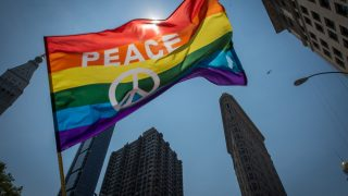 A participant waves a flag near the Flatiron Building during the 46th annual Gay Pride march June 26, 2016 in New York. New York kicked off June 26 what organizers hope will be the city's largest ever Gay Pride march, honoring the 49 people killed in the Orlando nightclub massacre and celebrate tolerance. / AFP PHOTO / the 46th / Bryan R. Smith