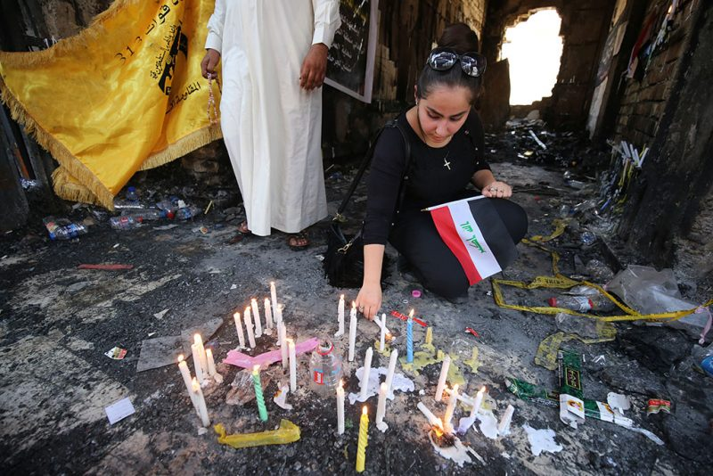 An Iraqi Christian woman lights a candle on July 8, 2016 at the site of a suicide bombing that ripped through Baghdad's busy shopping district of Karrada.The Baghdad bombing claimed by the Islamic State group killed 292 people, according to a new toll issued on July 7, many of whom were trapped in blazing buildings and burned alive. A suicide bomber detonated an explosives-laden minibus early on July 3, ahead of the Eid al-Fitr holiday marking the end of the holy Muslim fasting month of Ramadan. / AFP PHOTO / AHMAD AL-RUBAYE