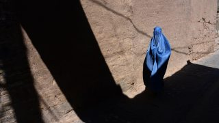 A burqa-clad Afghan woman walks through the old quarters of Herat on August 30, 2016.  / AFP PHOTO / AREF KARIMI