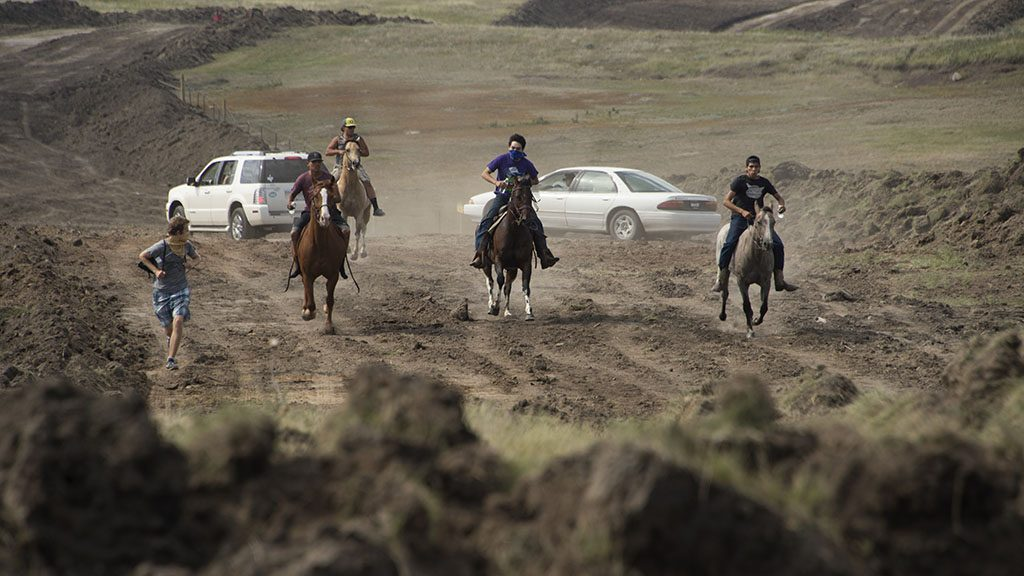 Protestors on horseback gallop away after members of the Standing Rock Sioux tribe and their supporters confronted a bulldozer crew and the private security team protecting the work site for the Dakota Access Pipeline (DAPL), near the Standing Rock Indian Reservation near Cannon Ball, North Dakota, September 3, 2016. 