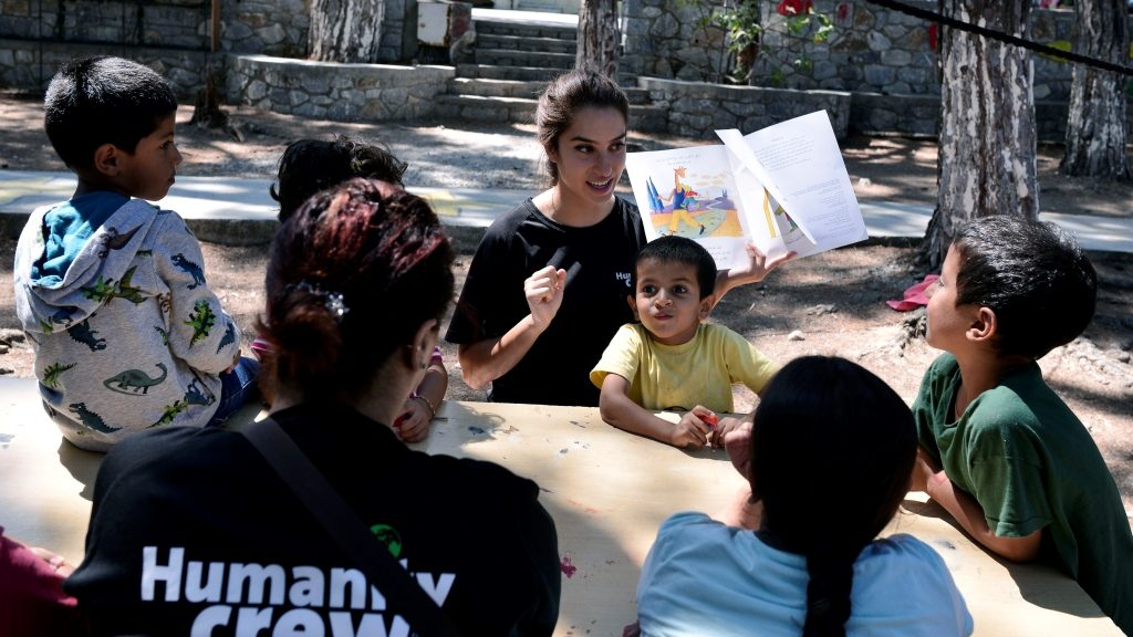 A picture taken on  August 31, 2016 shows children listening to a story read by a volunteer  at the ' Village All together' or PIKPA village on the island of Lesbos . More than 2,000 sea rescue volunteers, who last year saved thousands trying to cross the Mediterranean to Europe, have won the annual Nansen prize, the UN refugee agency announced on September 6, 2016. The Hellenic Rescue Team (HRT) will share the prestigious award with Efi Latsoudi, a human rights activist on Lesbos who helped provide a safe haven to thousands of refugees on the Greek island, the UN High Commissioner for Refugees said.  / AFP PHOTO / LOUISA GOULIAMAKI
