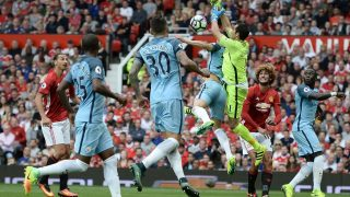 Manchester City's Chilean goalkeeper Claudio Bravo (3rd R) drops the ball as he bumps into Manchester City's English defender John Stones in the build up to Manchester United's first goal during the English Premier League football match between Manchester United and Manchester City at Old Trafford in Manchester, north west England, on September 10, 2016. / AFP PHOTO / Oli SCARFF / RESTRICTED TO EDITORIAL USE. No use with unauthorized audio, video, data, fixture lists, club/league logos or 'live' services. Online in-match use limited to 75 images, no video emulation. No use in betting, games or single club/league/player publications.  /