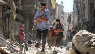 Syrian men carrying babies make their way through the rubble of destroyed buildings following a reported air strike on the rebel-held Salihin neighbourhood of the northern city of Aleppo, on September 11, 2016. Air strikes have killed dozens in rebel-held parts of Syria as the opposition considers whether to join a US-Russia truce deal due to take effect on September 12. / AFP PHOTO / AMEER ALHALBI