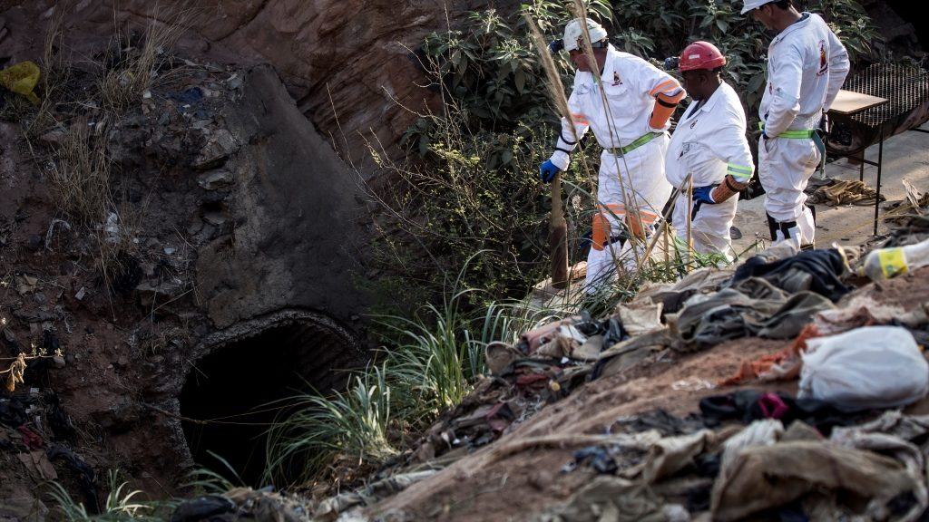 """Members of the Mine Rescue team looks at the entrance of the disused Langlaagte gold mine shaft entrance, where an unknown amount of """"Zama Zama's"""" (illegal miners) are trapped on September 11, 2016 in Johannesburg.  Emergency workers Sunday were striving to rescue illegal miners trapped underground in Johannesburg's oldest gold mine, a spokesman said. The diggers, whose numbers are unclear, are said to have been trapped in the disused mine since September 7.  / AFP PHOTO / JOHN WESSELS"""