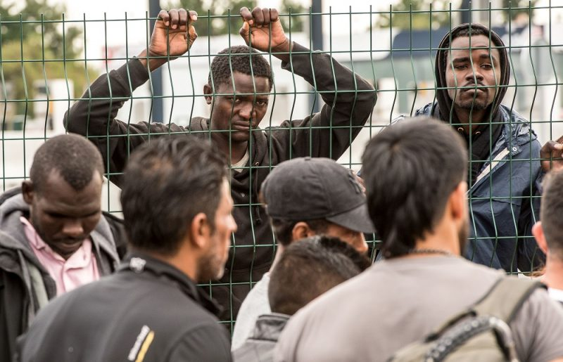 "Migrants from the 'Jungle' migrant camp who have been denied access to a bus heading to a ""Welcome and orientation centre"" (CAO) are pictured, on September 13, 2016 in Calais.  / AFP PHOTO / PHILIPPE HUGUEN"