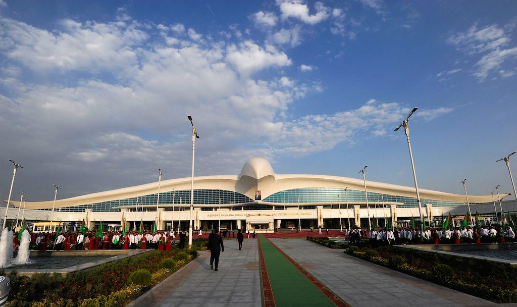 """People stand in front of a building of a new five-floor international airport in Ashgabat on September 17, 2016. Tightly-controlled Turkmenistan's President Gurbanguly Berdymukhamedov on September 17, 2016 hailed his country's """"solid transit potential"""" as he unveiled an international airport worth over $2 billion in the capital Ashgabat. / AFP PHOTO / IGOR SASIN"""