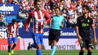 Atletico Madrid's French forward Antoine Griezmann (L) celebrates past Sporting Gijon's midfielder Nacho Cases after scoring during the Spanish league football match Club Atletico de Madrid vs Real Sporting de Gijon at the Vicente Calderon stadium in Madrid on September 17, 2016. / AFP PHOTO / GERARD JULIEN