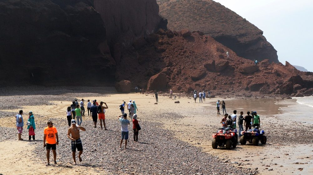 A general view shows Moroccans looking at the pile of red rubble after one of the famous arches of Legzira beach collapsed at a popular beach near Morocco's South West city of Sidi Ifini on September 24, 2016. The two immense rock arches were among Morocco's best-known natural wonders towering over Legzira beach on the Atlantic coast. / AFP PHOTO / STRINGER